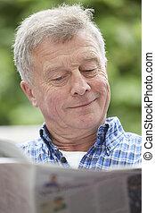 Senior Man Reading Newspaper Outdoors At Home