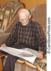 Senior man reading newspaper
