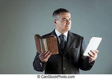 Senior man reading text from a modern tablet PC