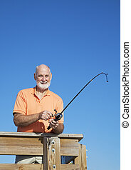 Senior Man Reels in Fish Vertical