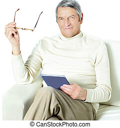 Senior man relaxing at home with in the book