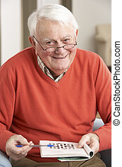 Senior Man Relaxing In Chair At Home Completing Crossword