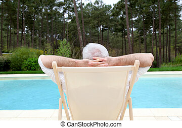 Senior man relaxing in deck chair by a pool