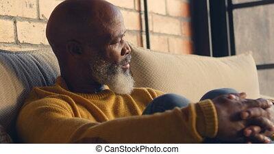 Senior man relaxing in living room 4k