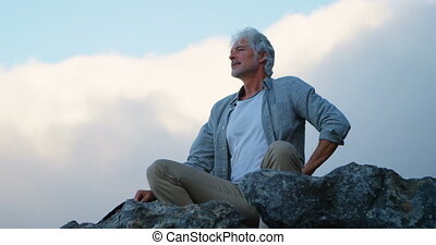 Senior man relaxing on a rock at countryside 4k - Active...