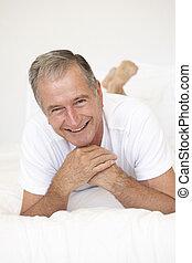Senior Man Relaxing On Bed