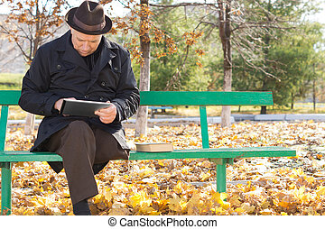 Senior man relaxing with a tablet computer