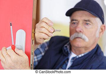 senior man repairing gate lock with screwdriver