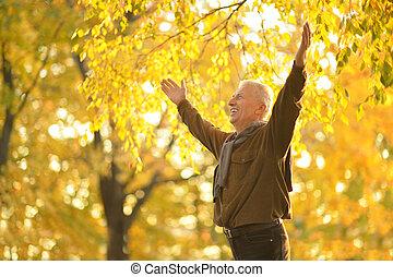 Senior man resting in the park in autumn