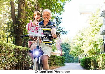 Senior man riding bicycle with granddaughter in his hands