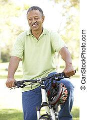 Senior Man Riding Bike In Park