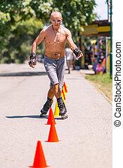 Senior man roller skating in park