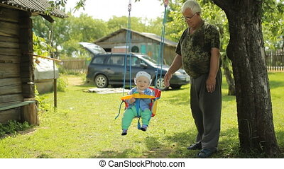 Senior man rolls the beautiful baby on a swing. Grandfather with his grandson in the garden of his home
