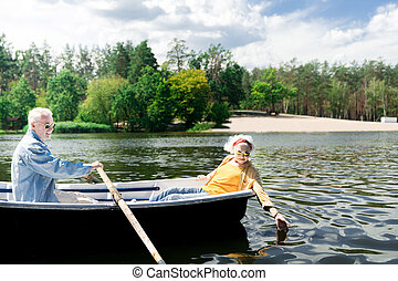 Senior man rowing the boat while his curious wife touching the water