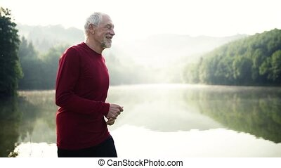 Senior man running by the lake outdoor in foggy morning in...