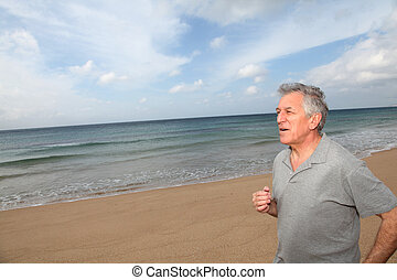 Senior man running on the beach