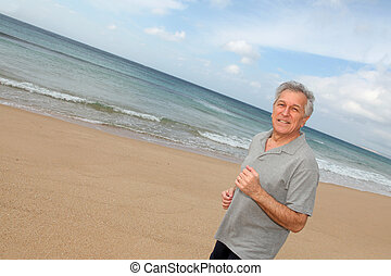 Senior man running on the beach