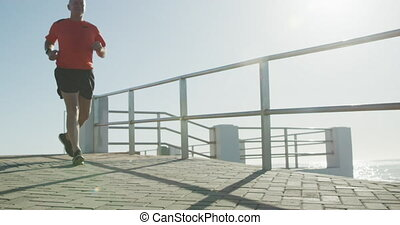 Senior fit Caucasian man working out on promenade by the sea wearing sports clothes, running on a sunny day in slow motion. Retirement healthy lifestyle activity.