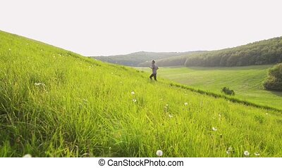 Senior man running outside up the green hill. - Active...