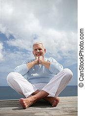 Senior man sat on a jetty