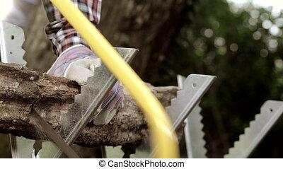 Senior man sawing a log handsaw closeup - Senior man sawing...