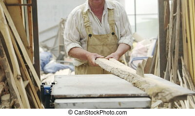 Senior man sawing wood on the machine with a circular saw
