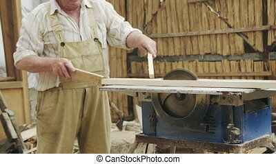 Senior man sawing wood on the machine with a circular saw -...