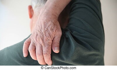 senior man scratching his back