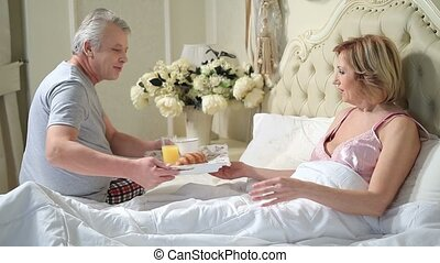 Senior man serving breakfast to woman in bed