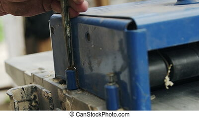 Senior man sets up woodworking equipment with screwdriver...