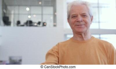 Senior man shakes car key in his hand