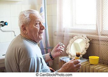 Senior man shaving his beard in bathroom in front of the...
