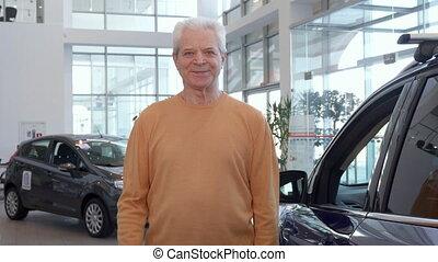 Senior man shows thumb up at the dealership