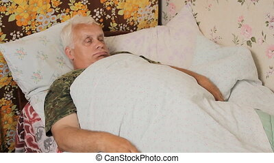 Senior man sick in bed with a huge thermometer. Funny thermometer under his arm