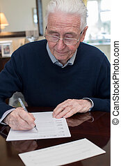 Senior Man Signing Last Will And Testament At Home