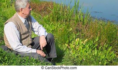 senior man sitting by pond and throwing pebble - Senior man...