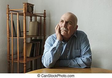 Senior man sitting deep in thought