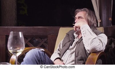 Senior man sitting in a chair drinking wine and smoking