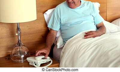 Senior man sitting in bed answering