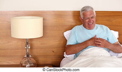 Senior man sitting in bed having a heart attack at home in...