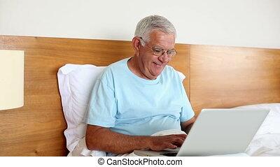 Senior man sitting in bed using lap