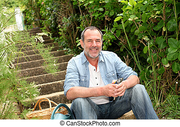 Senior man sitting in outdoor staircase