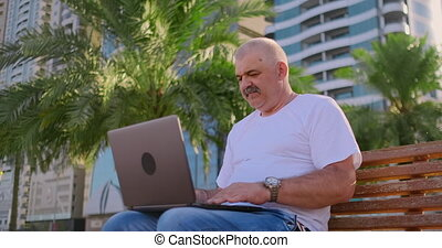 Senior man sitting in Park with palm trees with laptop in summer checks Bank account