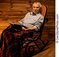 Senior man sitting in rocking chair in homely wooden interior with old book