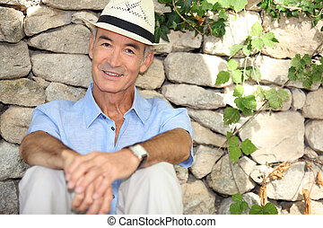 Senior man sitting in the shade of a stone wall