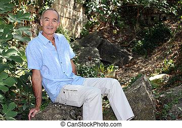 senior man sitting in the woods
