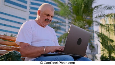 Senior man sitting on a Park bench among the palm trees and looking at laptop screen