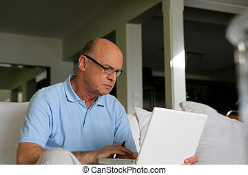 Senior man sitting on a sofa in front of a laptop computer