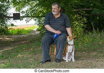 Senior man sitting on a stool next to his four-legged friend
