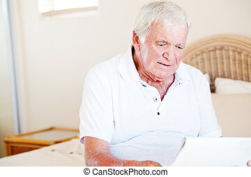 senior man sitting on bed and reading newspaper
